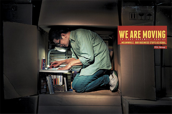 business moving print ad with man working inside cardboard packing box