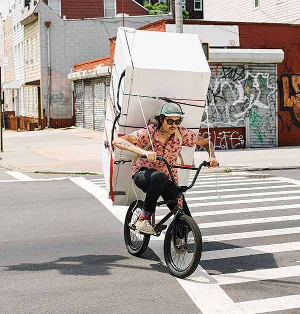 man hauling refrigerator on bicycle on city streets
