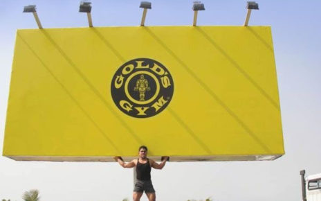 strong man holding up, lifting billboard - golds gym